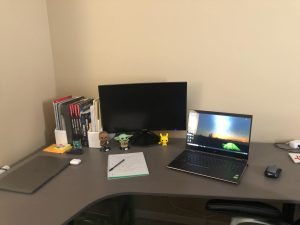 Corner desk with open laptop and second screen with a notebook and desk decor